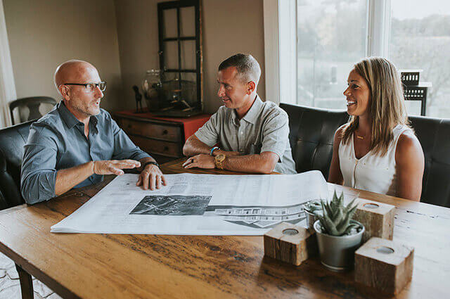 man discussing home addition plans with couple